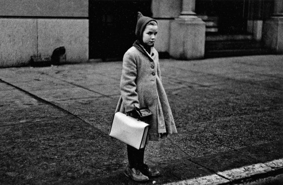 Girl with a pointy hood and white schoolbag at the curb, N.Y.C., 1957.